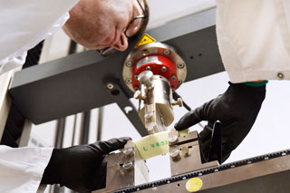 Mann in weißem Kittel beugt sich im Labor über Prüfgerät für Drei-Punkt-Biegeversuch