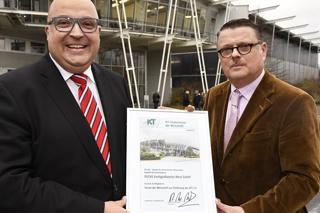 zwei Männer bei Überreichung einer Urkunde vor Gebäude