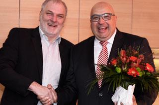 Zwei Männer beim Handshake mit Blumenstrauß
