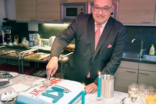 Mann mit Glatze, Brille und Anzug schneidet Torte an
