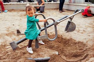 Kind auf Bagger im Sandkasten spielt Tiefbau