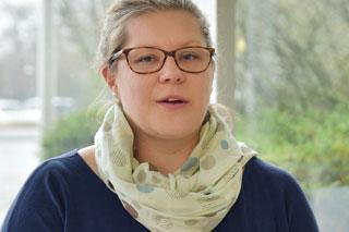 Frau mit Brille und Schal in Interviewsituation