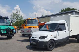 grüner Unimog, orangener Unimog, weißer Elektro-Transporter