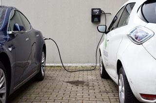 Zwei Elektrofahrzeuge blauer Tesla und weißer Renault Zoe werden mit Ladekabel geladen