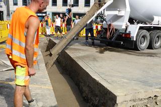 Bauarbeiter beobachtet Verfüllung eines Rohrgrabens mit Flüssigboden