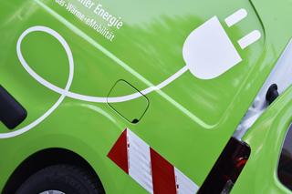 Grünes Auto mit Beklebung in Form eines Ladekabels mit Stecker