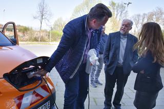 Man steckt Ladekabel in orangefarbenes Elektro-Nutzfahrzeug