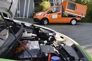 Elektromotor unter geöffneter Motorhaube und orangefarbenes Elektro-Nutzfahrzeug im Hintergrund