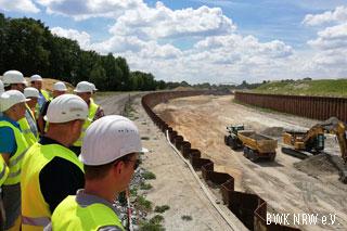 Menschen mit weißen Helmen und gelben Westen am Rand einer großen Baustelle