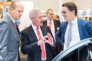 NRW-Verkehrsminister Hendrik Wüst spricht mit zwei Männern auf einem Messestand