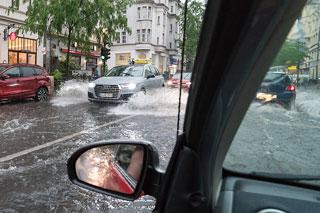 überflutete Straße mit Fahrzeugen vor Altbauhäusern aus Auto heraus fotografiert