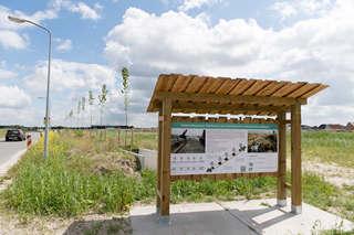 Holzstand mit Informationstafel vor Wiese mit Baumreihe