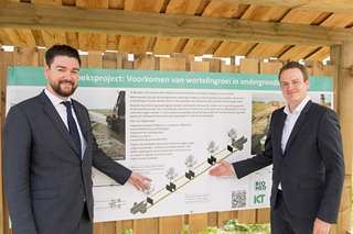 Zwei Männer in Anzügen zeigen auf Informationstafel