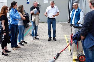 Teilnehmerinnen bei Produktvorführung eines Fräsroboters für den Kanal