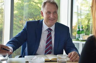 Mann in Anzug unterhält sich sitzend an Tisch