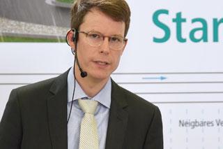 Mann mit Brille und Anzug hält einen Vortrag