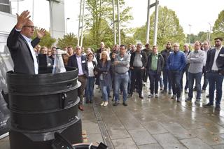 Mann steht gestikulierend in schwarzem Kunststoffschacht-Modul vor einer Gruppe Zuschauer