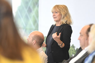 Blonde Frau mit dunklem Jackett spricht in Meeting