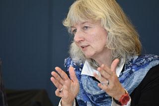 Blonde Frau mit blauem Schal gestikuliert