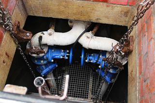 Blick in rechteckigen Schacht mit weißen Rohren und blauen Armaturen