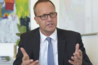 Mann mit Brille, Anzug und Krawatte gestikuliert