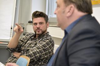 Mann mit dunklen Haaren, Bart und kariertem Hemd im Gespräch mit einem Mann in grauem Anzug