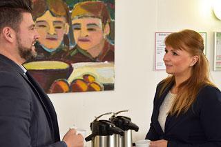Mann mit dunklen Haaren und Bart und Frau mit roten Haaren im Gespräch vor einem Bild mit Gesichtern