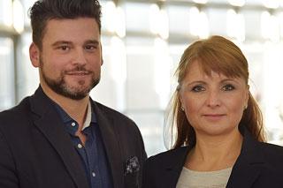 Mann mit dunklen Haaren und Bart und Frau mit roten Haaren schauen in die Kamera