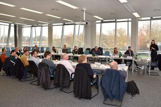 Teilnehmer eines Lehrgangs sitzen an Tischen in einem Seminarraum mit vielen Fenstern