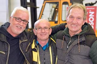 drei Männer in dicken Jacken Arm in Arm schauen in Kamera
