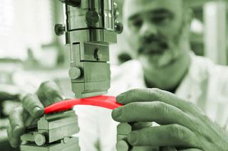 Mann mit Bart legt rote Materialprobe in Prüfgerät ein