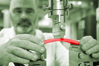 Mann mit Bart legt rote Materialprobe auf Prüfgerät