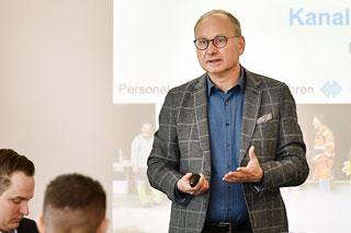 Mann mit Brille, blauem Hemd und kariertem Sakko hält Vortrag