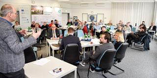 Teilnehmer einer Veranstaltung sitzen in einem Vortragssaal