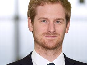 Portrait Mann mit rotblonden Haaren, blauen Augen und kurzem Bart mit Anzug und Krawatte