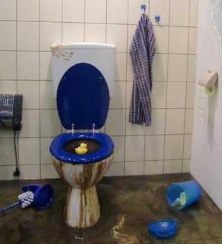mit braunem Abwasser überflutetes Badezimmer mit Kloschüssel mit blauem Deckel und gelbem Entchen
