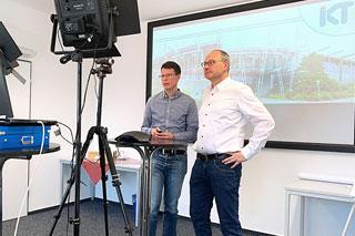 zwei Männer vor einem Bildschirm wärend einer Web-Präsentation