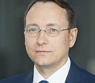 Portrait eines Manns mit Brille und blauem Anzug