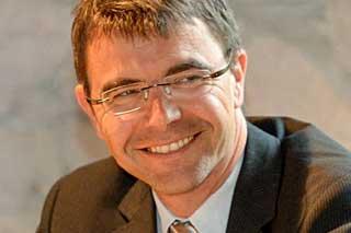 Mann mit Brille und Anzug lächelt