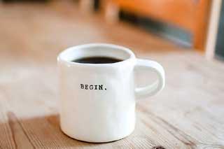 weiße Kaffeetasse auf Holztisch