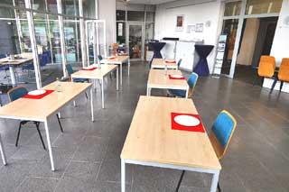 Holztische mit roten Platzsets und weißen Tellern auf grauem Steinboden