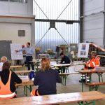 mehrere Personen in Arbeitskleidung sitzen an Tischen