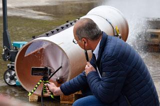Mann hockt vor Kanalrohr und filmt Test einer Kanalreinigungsdüse mit dem Smartphone