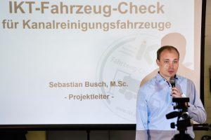 Mann mit hellblauem Hemd vor Projektion mit Mikrofon