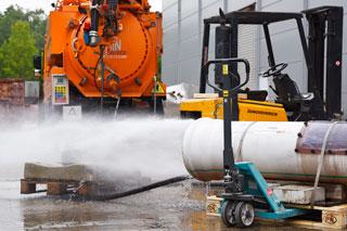 Wasser schießt aus Rohr vor orangefarbenem Kanalreinigungsfahrzeug
