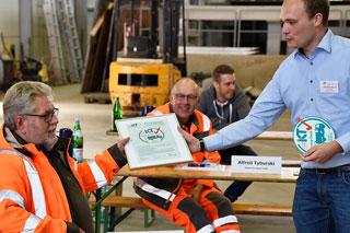 mann in hellblauem Hemd überreicht Urkunde an Mann in orangefarbener Arbeitskleidung