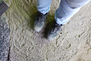 Person steht mit Arbeitsschuhen auf verfestigtem Flüssigboden