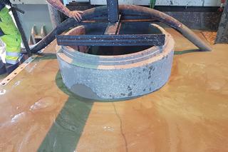 Arbeiter hält Einfüllschlauch für Flüssigboden in Versuchsstand