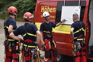 Feuerwehrleute bei der Einsatzbesprechung vor dem Einsatzfahrzeug
