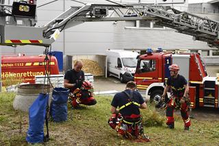 Feuerwehrleute bei einer Übung vor einem Einsatzfahrzeug mit Drehleiter